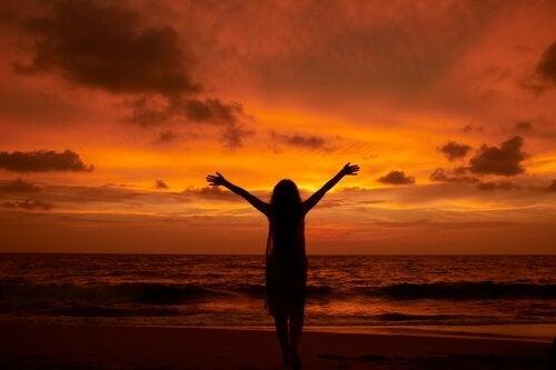Frau am Meer streckt ihre Arme gen Himmel