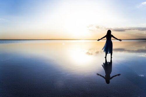 Frau mit offenen Armen am Meer
