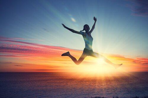 Frau springt Meer im Hintergrund