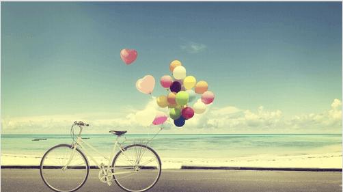 Fahrrad mit Luftballons am Strand