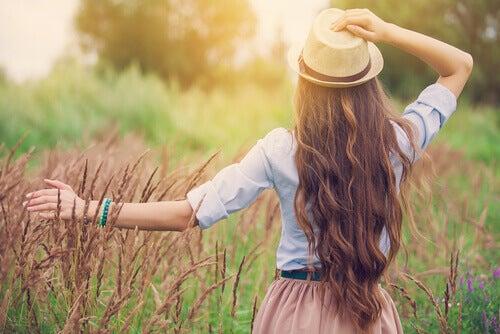 Frau mit Hut laeuft durch ein Feld