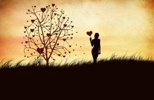 Umgang mit Gefühlen - Frau mit herzförmigem Ballon neben einem Baum der Gefühle