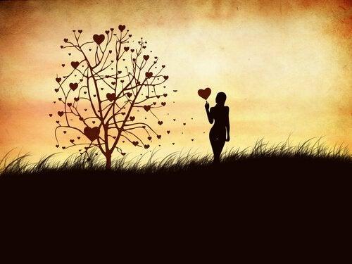 Frau-mit-herzfoermigem-Ballon-neben-Baum-der-Gefuehle