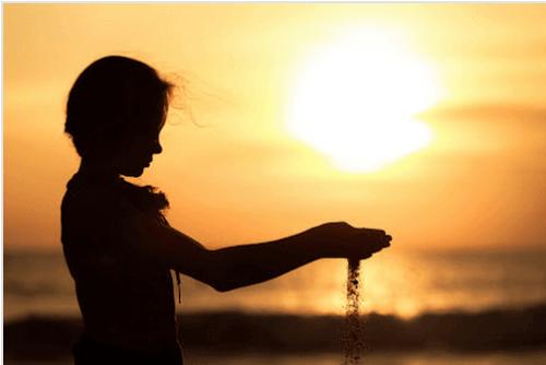 Kind-laesst-Sand-durch-Haende-rinnen