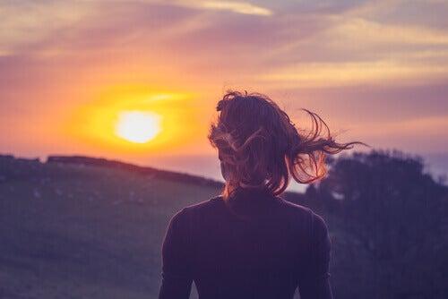Frau-sieht-Sonnenuntergang-in-den-Bergen