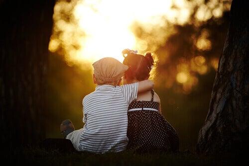 Junge-sitzt-umarmt-Maedchen-Sonnenuntergang