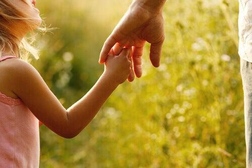 Maedchen greift nach Hand vom Vater