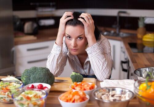 Nervöse Frau sitzt am Tisch voller Essen