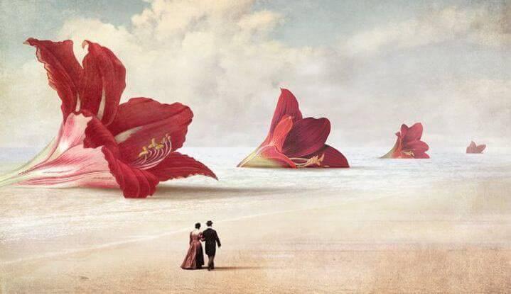 Paar-geht-am-Strand-mit-Riesenblumen-spazieren