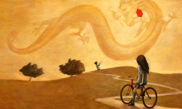 Maedchen auf Fahrrad schaut zu Junge mit Drachen