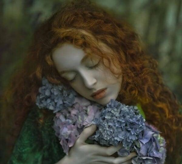 Rothaariges Mädchen umarmt Blumen