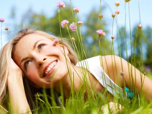 Frau liegt auf einer Blumenwiese