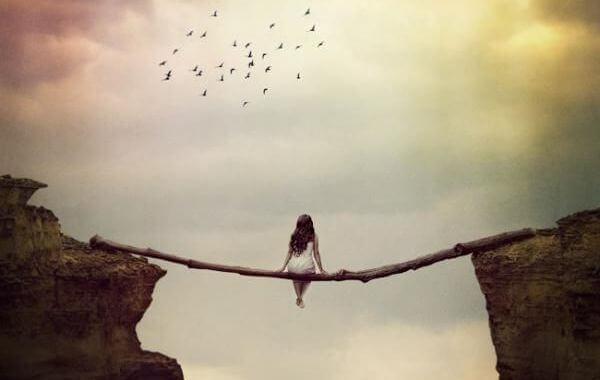 Frau sitzt auf Baumstamm und schaut in den Himmel