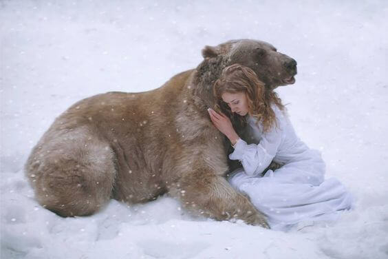 Frau umarmt einen Baer