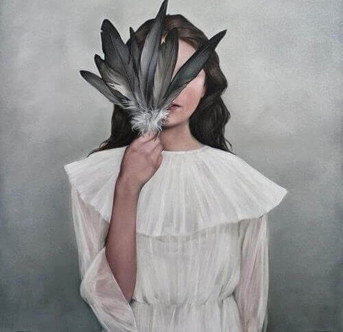 Frau versteckt ihr Gesicht hinter Federn