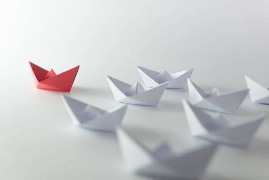 Rotes Papierschiff führt Gruppe weißer Papierschiffe