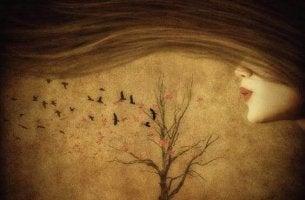 Frau blaest Blätter des Baumes hinfort