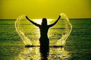 Eine Frau mit erhobenen Armen steht im Meer vor der Sonne