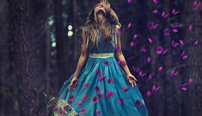 Frau im Wald mit lila Schmetterlingen