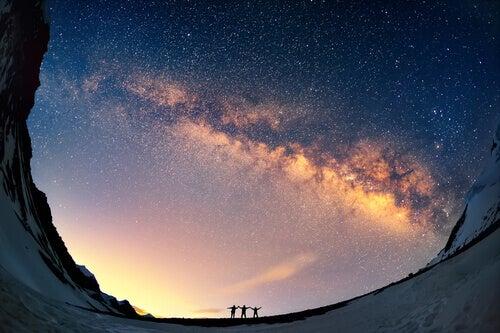 Träume entdecken und Realität werden lassen - Freunde stehen in den Bergen unter einem tollen Sternenhimmel