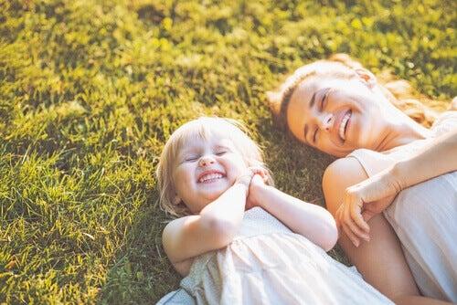 Mutter und Tochter laechelnd auf Wiese