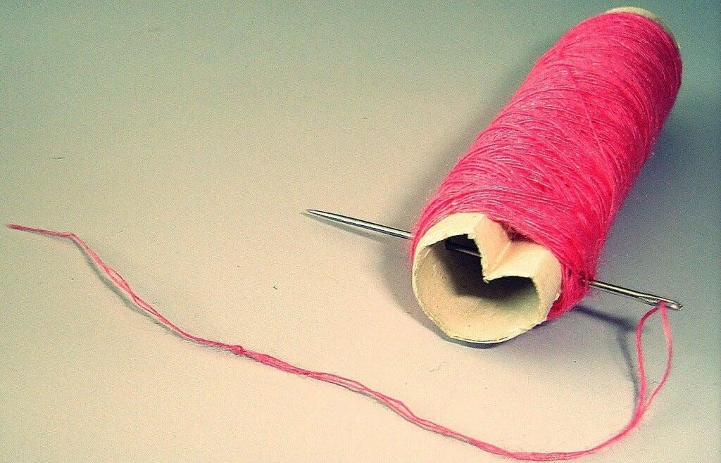 Nadel und Faden um eine herzförmige Garnrolle