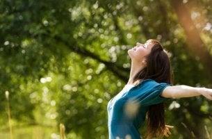 Sich mit der Natur verbinden - Frau füllt ihre Lungen mit frischer Luft