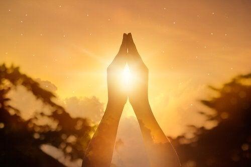 Gefaltete Hände vor Sonnenuntergang