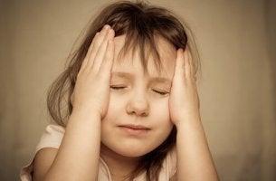 Traumatische Kindheitserfahrungen - Kind stützt seinen Kopf auf seine Hände