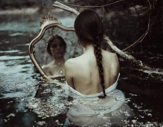 Frau mit Depressionen betrachtet sich im Spiegel und ertrinkt dabei fast
