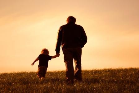 Opa läuft mit seinem Enkel über ein Feld