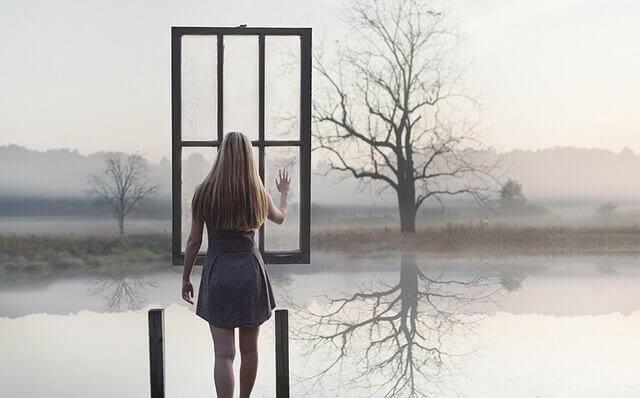 Frau berührt Fenster zum See