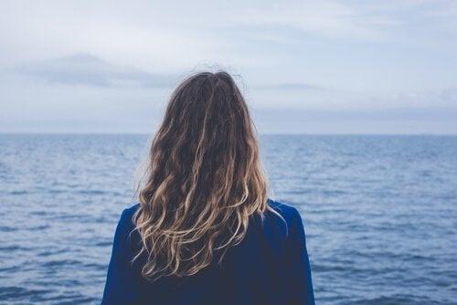 Frau schaut aufs offene Meer
