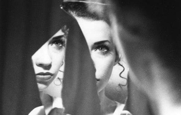Frau steht vor einem Spiegel