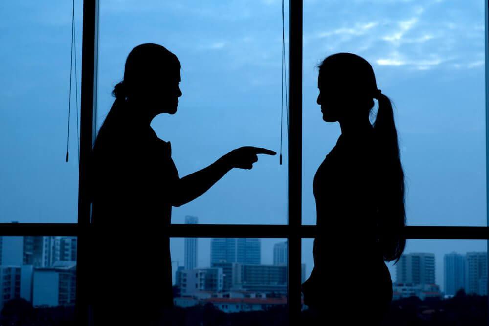 Frau zeigt mit ihrem Finger auf ihr Gegenueber