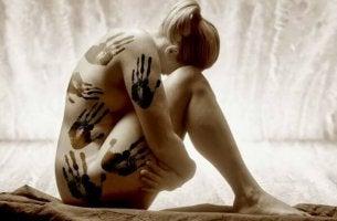 Nein zu Gewalt gegen Frauen - Nackte Frau, auf der Handabdrücke zu sehen sind