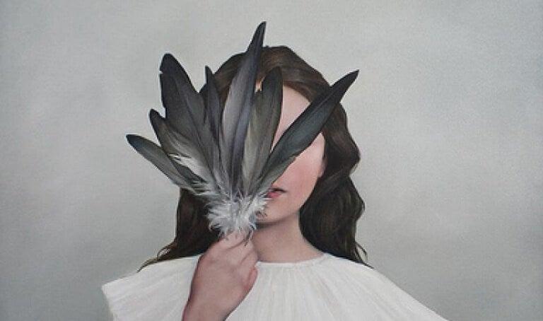 Hochsensible Frau mit schwarzen Federn vorm Gesicht