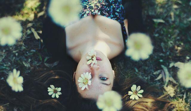 Junge Frau umgeben von Blumen