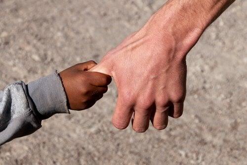 Kinderhand hält sich am Daumen eines Erwachsenen fest