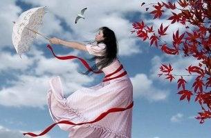 Mädchen hält im Sturm am Schirm fest, aber wer nicht loslassen kann, kann auch nicht nach dem Glück greifen.