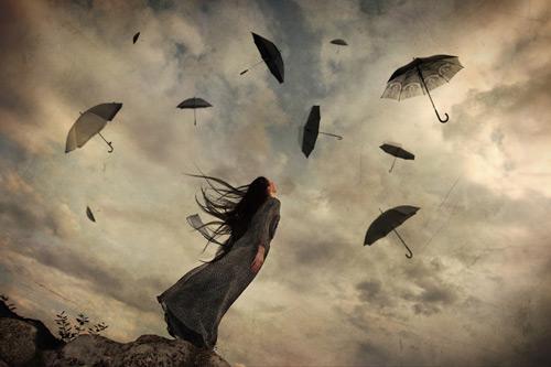 Regenschirme fliegen am bewölkten Himmel