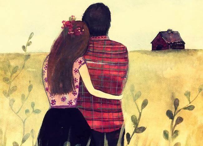 Sich umarmendes Paar schaut über das Feld zum Haus