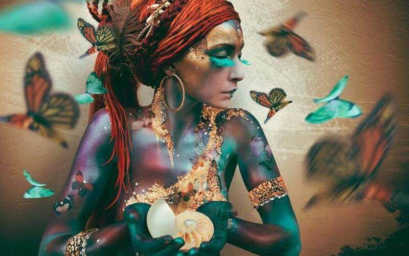 Bezaubernde Frau mit Schmetterlingen und Muschel in der Hand