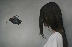 Eine Frau schaut einem Vogel ins Gesicht