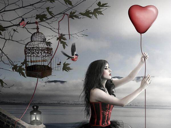 Frau vor einem Vogelkäfig lässt Ballon steigen