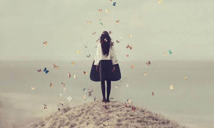 Frau steht auf einem Hügel und ist von Schmetterlingen umgeben