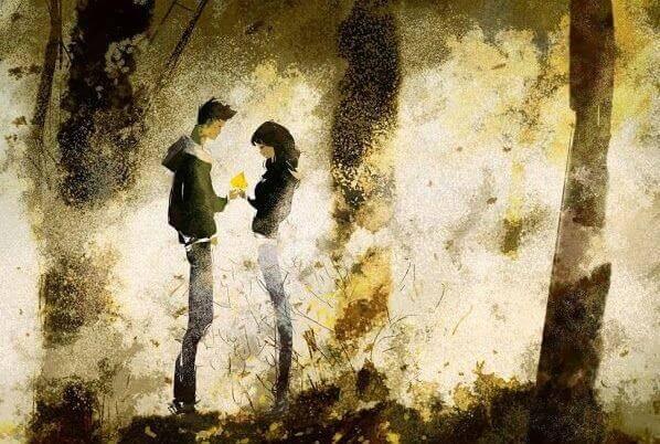 Paar steht im Wald und schaut auf ein Geschenk, das übergeben wird.