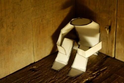 figur-aus-papier-sitzt-in-der-ecke