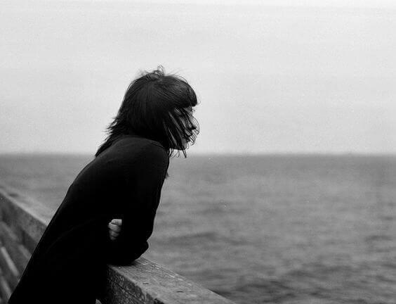 Eine einsame Frau blickt auf das Meer.