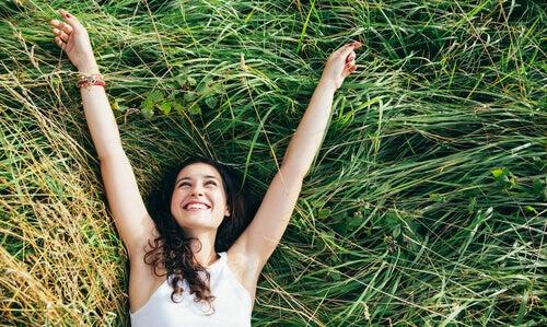 Eine Frau entspannt sich im Gras und ist glücklich.